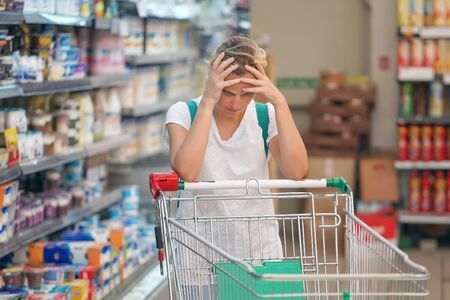 Upset woman in a supermarket with an empty shopping trolley. Crises, rising prices for goods and products. Woman shopping at the supermarket. Foto de archivo