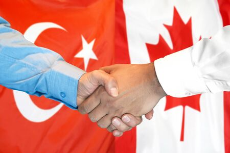 Business handshake on the background of two flags. Men handshake on the background of the Turkey and Canada flag. Support concept