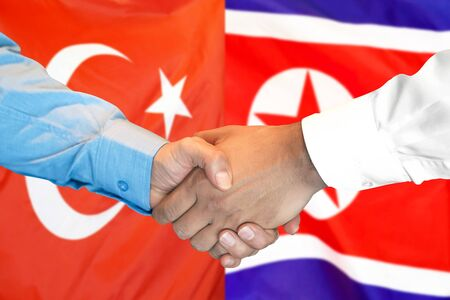 Business handshake on the background of two flags. Men handshake on the background of the Turkey and North Korea flag. Support concept Stok Fotoğraf