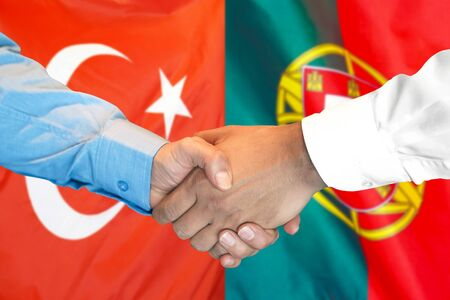 Business handshake on the background of two flags. Men handshake on the background of the Turkey and Portugal flag. Support concept