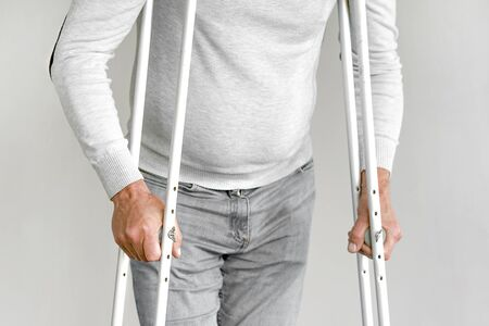 Elderly man on crutches on a gray background. Close-up a elderly man walking with crutches. Stok Fotoğraf