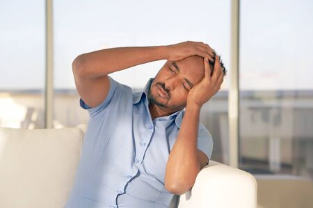 African Man suffering from headache migraine pain at home on sofa. Male holds head with hand. Concept of health.