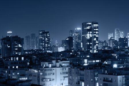 Nocny widok na życie miasta. Światło budynków lśniące chłodnymi niebieskimi tonami. Widok na scenę nocną w Tel Awiwie, Izrael. Krajobraz miasta niebieski odcień. Zdjęcie Seryjne