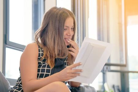 The girl reads a letter with good news sitting on the couch. Woman enjoying good news in writing. An euphoric girl is happy after reading good news in a written letter, approving a loan.