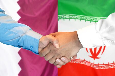 Business handshake on the background of two flags. Men handshake on the background of the Qatar and Iran flag. Support concept