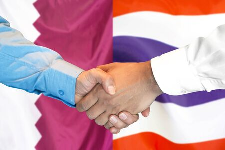 Business handshake on the background of two flags. Men handshake on the background of the Qatar and Thailand flag. Support concept 写真素材