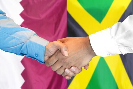 Business handshake on the background of two flags. Men handshake on the background of the Qatar and Jamaica flag. Support concept