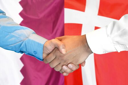 Business handshake on the background of two flags. Men handshake on the background of the Qatar and Denmark flag. Support concept 写真素材