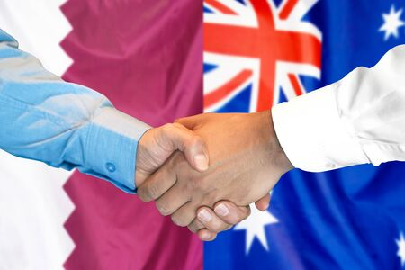 Business handshake on the background of two flags. Men handshake on the background of the Qatar and Australia flag. Support concept 写真素材