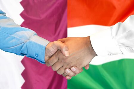 Business handshake on the background of two flags. Men handshake on the background of the Qatar and Hungary flag. Support concept 写真素材