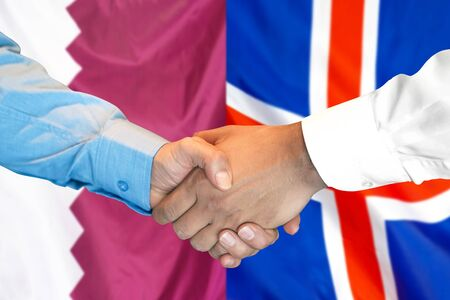 Business handshake on the background of two flags. Men handshake on the background of the Qatar and Iceland flag. Support concept 写真素材