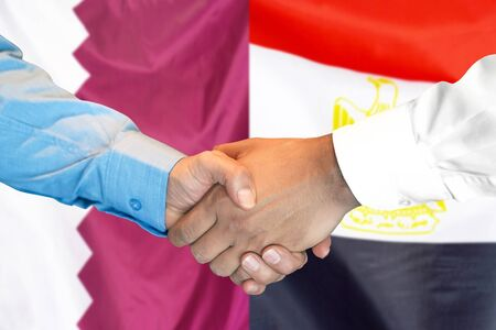 Business handshake on the background of two flags. Men handshake on the background of the Qatar and Egypt flag. Support concept