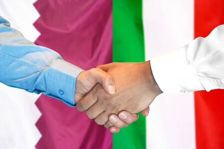 Business handshake on the background of two flags. Men handshake on the background of the Qatar and Italy flag. Support concept 写真素材