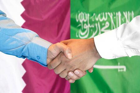 Business handshake on the background of two flags. Men handshake on the background of the Qatar and Saudi Arabia flag. Support concept