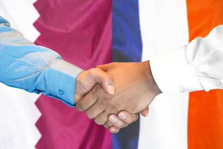 Business handshake on the background of two flags. Men handshake on the background of the Qatar and France flag. Support concept
