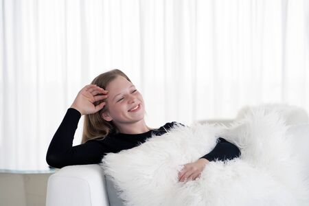 Relaxed young blonde girl enjoying rest on comfortable sofa, calm attractive woman relaxing on sofa, breathing fresh air meditating at home, peace of mind, copy space