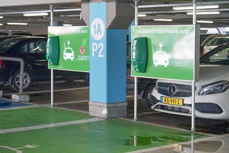 Electric car charging on parking lot with electric car charging station. Close up of power supply plugged into an electric car being charged. 7 September 2018. Rotterdam. Netherlands Banque d'images - 137812319