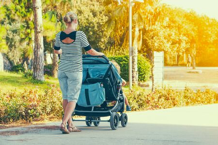 Woman with a baby carriage for two children walks in the park on a summer morning. Young mom with baby carriage. Walking. Back view. Toning.