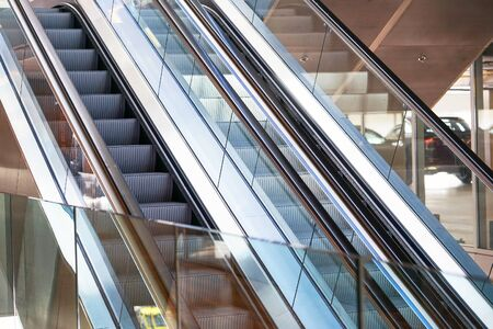 Escalators in an office building. Empty escalator stairs. Modern escalator in shopping mall, Department store escalator. Empty escalator inside a glass building. Stockfoto