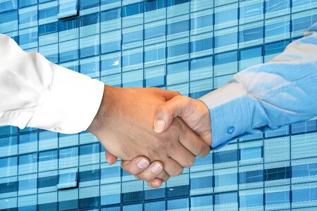 Businessmans partnership handshaking process. Skyscraper on the background