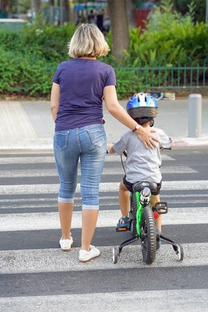 Mother goes pedestrian crossing with childr on bicycle. A woman with child crossing the road in the city. Back view.                                                                  Stock Photo