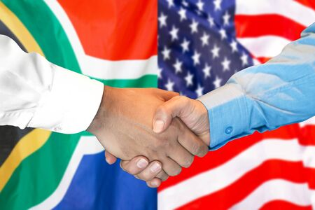 Business handshake on the background of two flags. Men handshake on the background of the South Africa and United States of America flag. Support concept