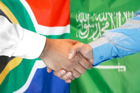 Business handshake on the background of two flags. Men handshake on the background of the South Africa and Saudi Arabia flag. Support concept