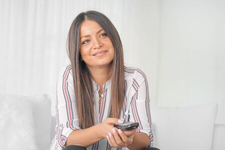 Portrait of happy young woman sitting on sofa with tv remote control. Smiling woman with remote control on sofa.