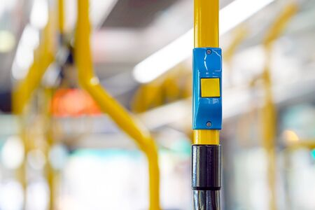 Yellow stop button for bus or tram. Press the button to request the bus driver for get off at the next station. Public transport transfer.
