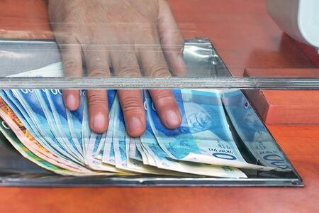 Cash money israeli shekel, at bank office or currency exchanger. Male hand with shekel money in cash department window. Currency exchange concept. Clerk giving cash  israeli shekel money to customer at bank office.