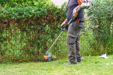 Professional gardener using an edge trimmer in the city parck. Elderly man worker mowing lawn with grass trimmer outdoors on sunny day.