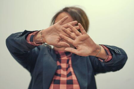 Woman hide her face at hand isolated on white background. Woman holding her hand stretched out toward the camera, covering her face, avoiding to be seen or stopping a problems