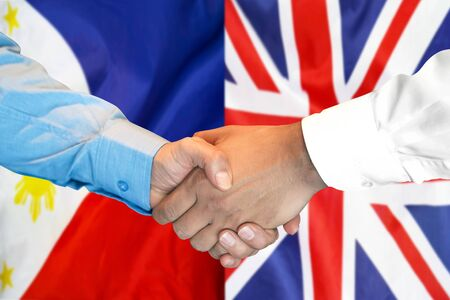 Business handshake on the background of two flags. Men handshake on the background of the Philippines and United Kingdom flag. Support concept Stock fotó