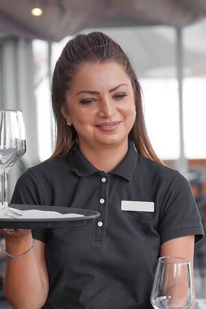 Portrait of waitress carries wine glasses to the client in the hotel restaurant. Closeup of a tray with empty wine glasses. Morning time. The concept of service.
