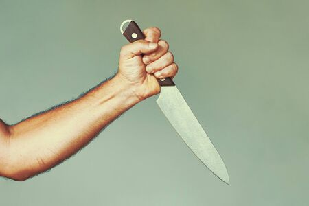 Hand of caucasian man holding a knife isolated on a gray background. Man hold knife - aggression. Big kitchen knife in man hand. Large kitchen knife in a mans hand.