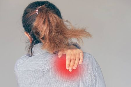 Woman suffering from neck pain isolated on gray background. A womans sense of fatigue, exhausted, stressed.  Girl massages her painful neck with her hands. The concept of body and health. Tired neck. Zdjęcie Seryjne
