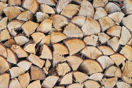 Chopped firewood combined to dry for the winter. The firewood combined in two ranks for a furnace kindling. Firewood combined in a woodpile. Texture Zdjęcie Seryjne