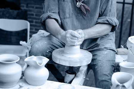 Close-up hands male creating cans or vases of gray clay. Mans hands make a clay pitcher, macro. Potter makes a pitcher. Zdjęcie Seryjne