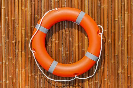 Orange lifebuoy pool ring hanging on a bamboo wall for emergency response, when people submerging in the water, almost near the pool and the beach. Life ring in swimming pool.