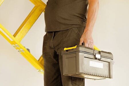 Electrician holds tool box and yellow wooden ladder. The builder carries a wooden ladder and toolbox on a gray background. Breeder with tool box and yellow wooden ladder.