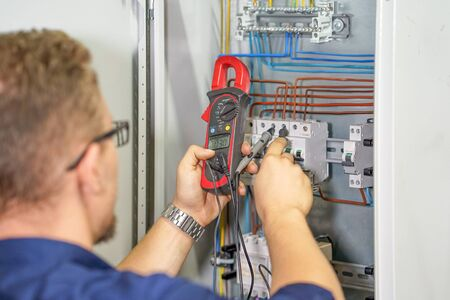 Electrician man measures voltage with multimeter in electrical cabinet. An electrician is checking the voltage in an electric box. Adjustment of electrical control circuit for industrial equipment. Toning