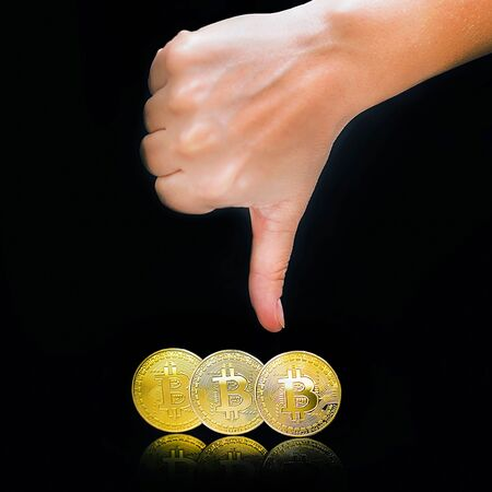 Female arm show thumb down sign. Thumb down hand sign. Bitcoin price fall. Fall Bitcoins and new Virtual Fall money concept.