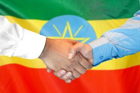 Business handshake on Ethiopia flag background. Men shaking hands and Ethiopia flag on background. Support concept Zdjęcie Seryjne