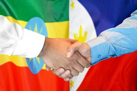 Business handshake on the background of two flags. Men handshake on the background of the Ethiopia and Philippines flag. Support concept Zdjęcie Seryjne