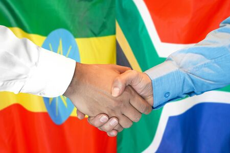 Business handshake on the background of two flags. Men handshake on the background of the Ethiopia and South Africa flag. Support concept