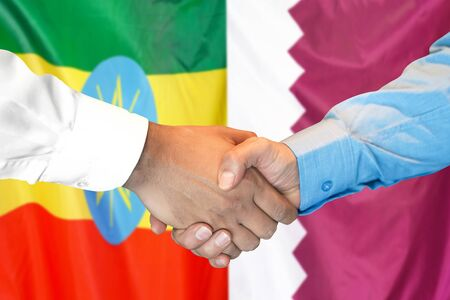 Business handshake on the background of two flags. Men handshake on the background of the Ethiopia and Qatar flag. Support concept Zdjęcie Seryjne
