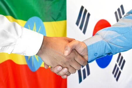 Business handshake on the background of two flags. Men handshake on the background of the Ethiopia and South Korea flag. Support concept