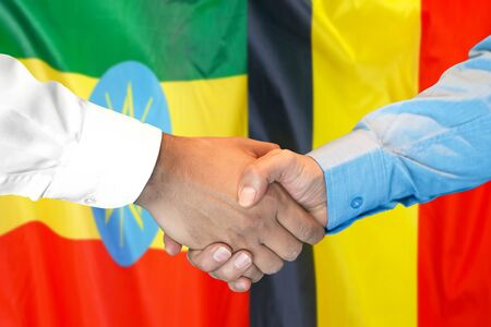 Business handshake on the background of two flags. Men handshake on the background of the Ethiopia and Belgium flag. Support concept