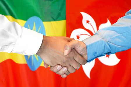 Business handshake on the background of two flags. Men handshake on the background of the Ethiopia and Hong Kong flag. Support concept Zdjęcie Seryjne