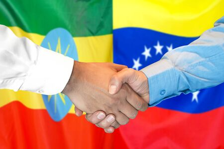 Business handshake on the background of two flags. Men handshake on the background of the Ethiopia and Venezuela flag. Support concept